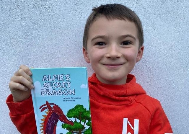 Jacob Carnes, 8, is pictured with his book called Alfie's Secret Dragon.