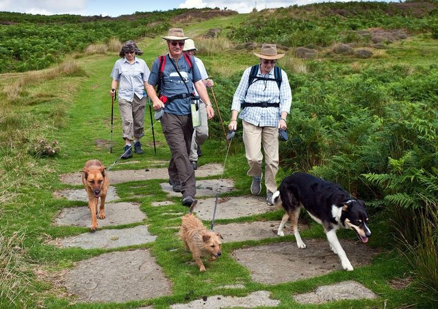 People with dogs on a lead on path at Dundale.