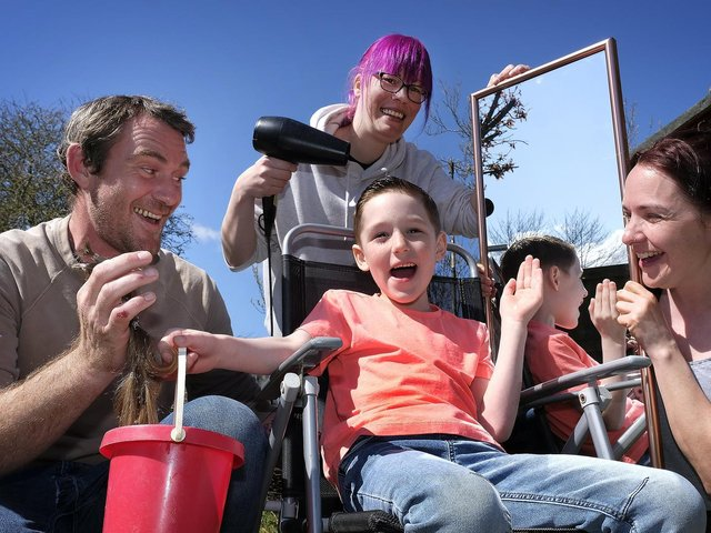 Dara Whitefield completes his charity haircut with Kerry Ward performing the trim, watched by dad Jamie and mum Siobhan.