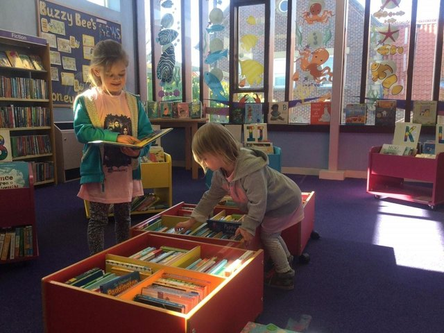 Excited young visitors happily looking for new books in Whitby Library's junior section.