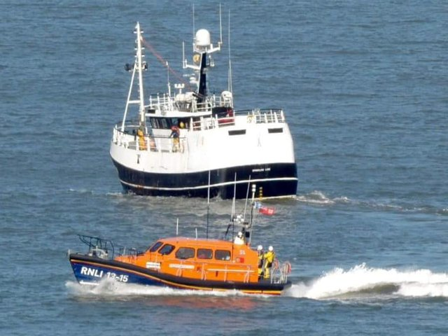 The lifeboat near the fishing vessel.