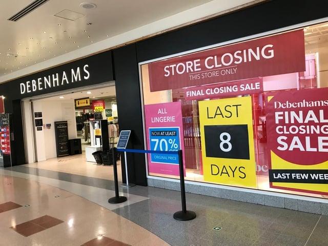 Poster in window displays countdown to Debenhams store closure.
