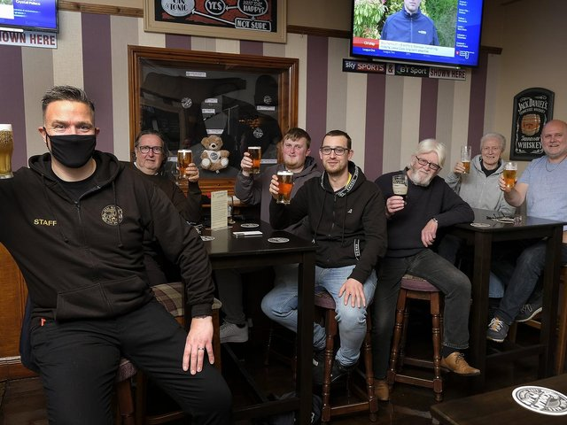 Landlord Danny Smith, left, celebrates with customers at Scholars Bar.