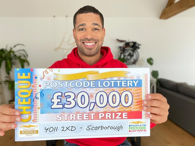 Danyl Johnson with the winning cheque. Picture: People's Postcode Lottery